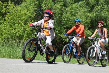 ni�os en bicicleta: Retrato de bicicleta de caballo chico feliz en el parque con sus padres detr�s Foto de archivo
