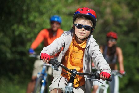 Portrait of happy boy riding bicycle in the park with his parents behind photo