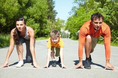 enfant qui court: Portrait de famille de trois personnes debout sur le d�but avant d'ex�cuter Banque d'images
