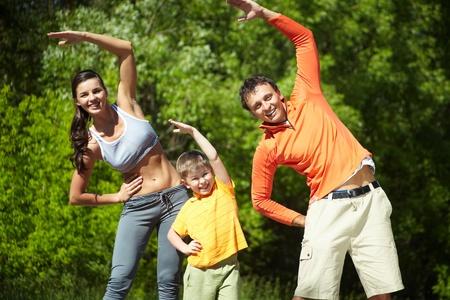 aktywność fizyczna: Portret rodziny trzech robić ćwiczenia fizyczne w parku
