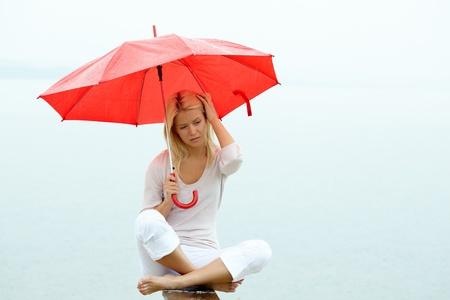 Portrait of sad young woman sitting with umbrella under rain photo