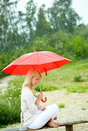 Portrait of sad young girl with umbrella sitting on bench photo