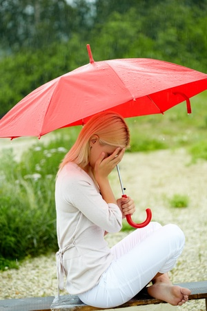 Portrait of sad young girl sitting on bench with umbrella photo