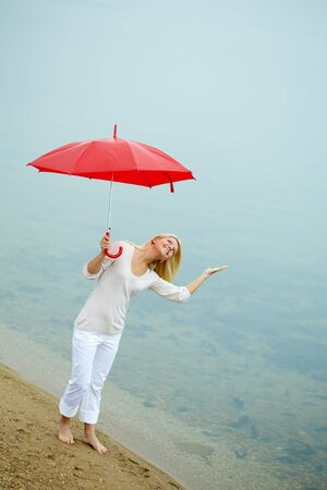 Portrait of happy young girl on the shore with umbrella photo