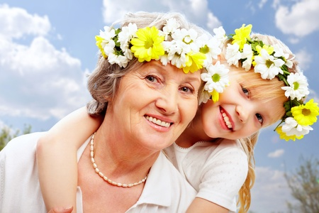 Portrait of granddaughter embracing her grandmother on a blue background     photo