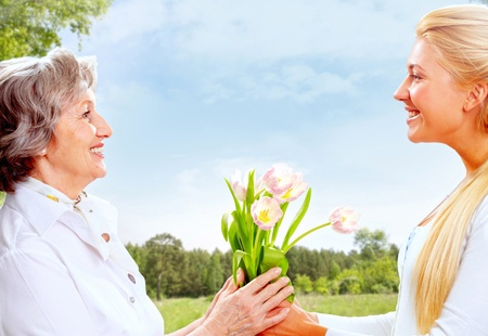 the old days: Portrait of young woman giving tulips to her mother    Stock Photo