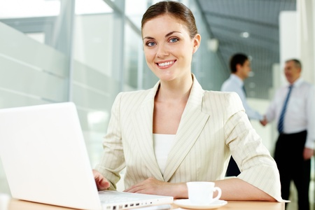 A beautiful businesswoman looking at camera with handshaking men on background Stock Photo - 9910609