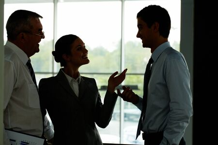 Silhouettes of three partners interacting with each other in office photo