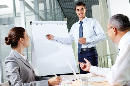 Smiling business man presenting new project to his partners on a whiteboard photo