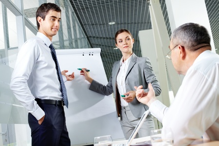 Two young associates by whiteboard looking at senior chief at meeting Stock Photo - 9910613