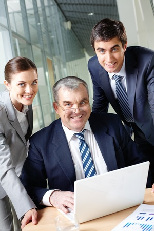 A business team of three looking at camera at workplace Stock Photo - 9910637