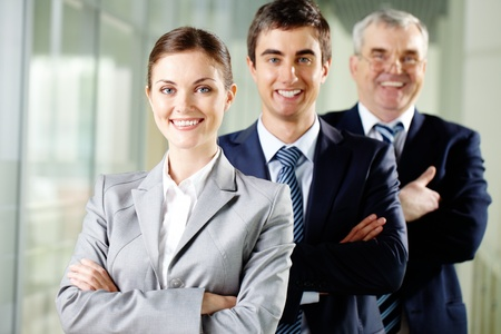 Smiling businesswoman looking at camera with two men behind photo