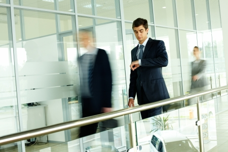 Businessman looking at watch with walking people on background Stock Photo - 9910581