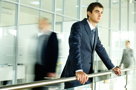 go inside: Businessman standing by banisters with walking people on background