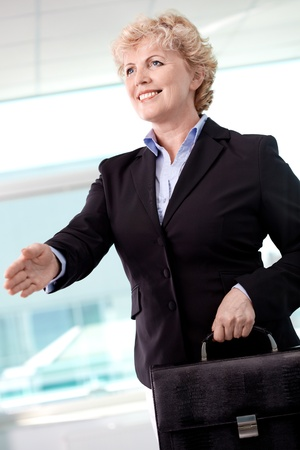 Portrait of smiling middle aged businesswoman with briefcase giving her hand for a handshake photo