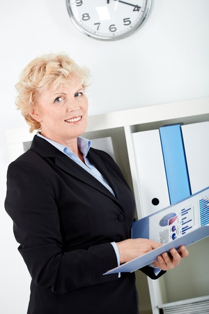 Portrait of smiling middle aged businesswoman with document looking at camera photo