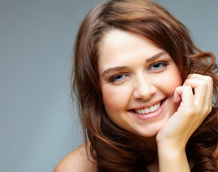 Portrait of happy female touching her face and laughing photo