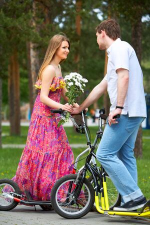 Happy woman with bunch of flowers and her boyfriend on scooters in park photo