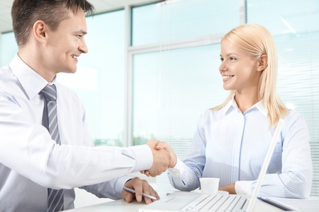 Portrait of successful associates handshaking after striking deal Stock Photo - 9910711