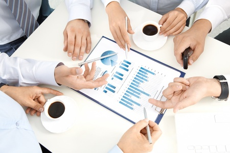 Image of human hands with pens over business documents at meeting photo