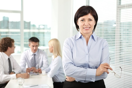 Mature businesswoman looking at camera in working environment photo