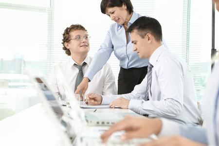 Group of business partners listening to mature woman explaining her idea at meeting Stock Photo - 9910703