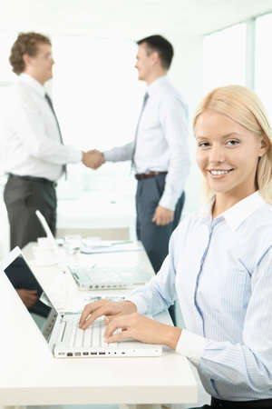 A beautiful businesswoman looking at camera with handshaking men on background photo