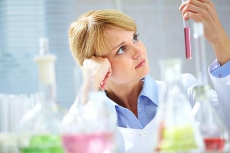 material de vidrio: Un joven qu�mico mirando ondeante tubos con l�quido Foto de archivo