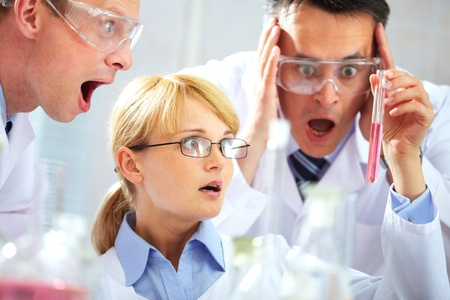 Three chemists looking shocked at a tubing and shouting in joy Stock Photo - 9910724