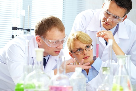 Three chemists researching liquid in tubing photo