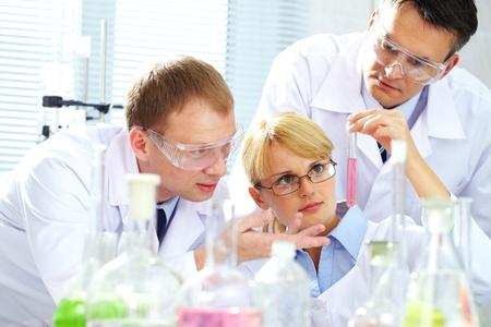 laboratorio clinico: Tres qu�micos investigando l�quido en tubos