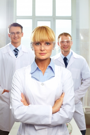 Portrait of female doctor standing in front of her male colleagues  photo