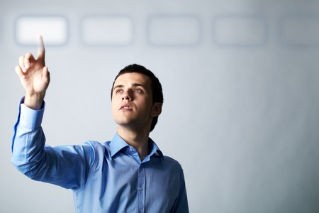career choices: Image of young businessman pointing at virtual button