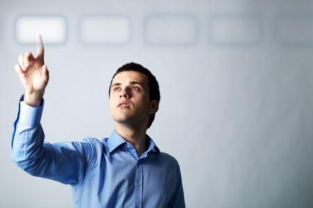 seguridad en el trabajo: Imagen de joven empresario apuntando al bot�n virtual  Foto de archivo