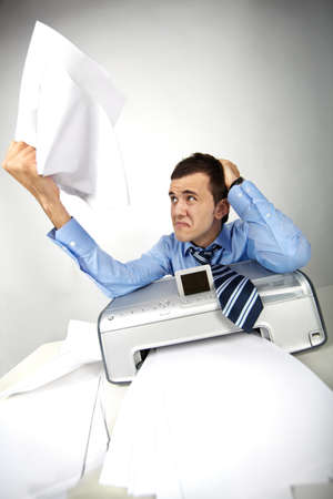 Portrait of nervous businessman holding printed papers photo