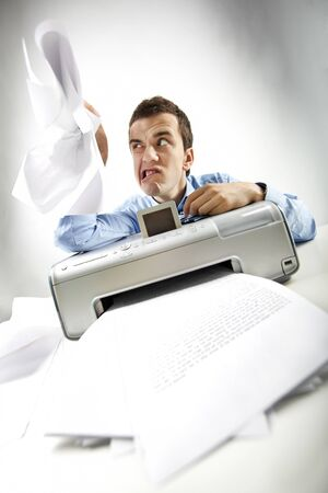 Portrait of annoyed businessman holding papers printed by scanner photo