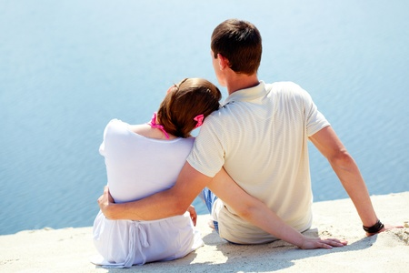 Backs of peaceful couple sitting on sandy shore in front of blue water Stock Photo - 9910838