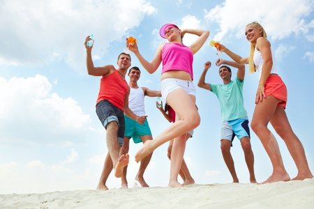 Portrait of happy young friends with cocktails dancing at beach party Stock Photo - 9910797