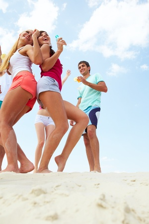 Portrait of joyful young friends dancing at beach party Stock Photo - 9910779