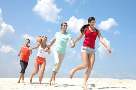 four person: Four friends walking on beach holding hands  Stock Photo