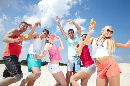 fiesta amigos: Seis amigos bailando en la playa con c�cteles