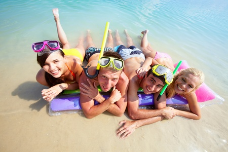 resting mask: Four friends in scubas lying on sand by water Stock Photo