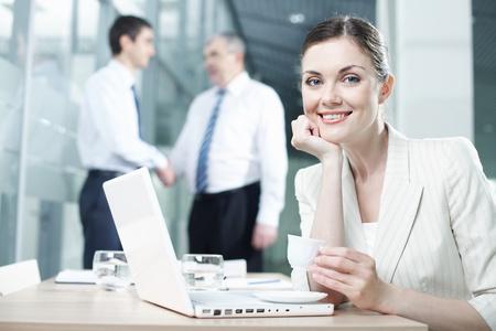 Portrait d'une jolie femme assise à table avec un ordinateur portable