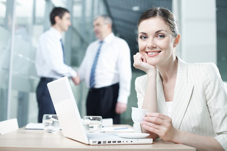 business environment: Portrait of a pretty woman sitting at table with laptop