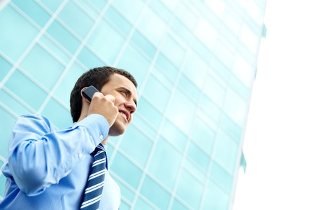Portrait of a young businessman standing by office building and talking on the phone  photo