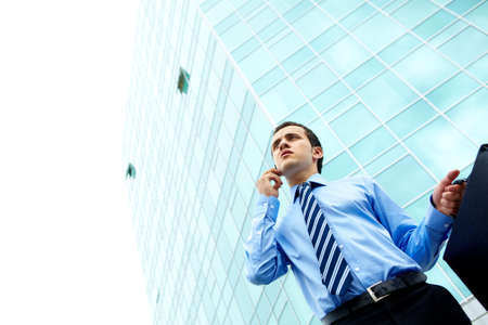 Businessman standing by office building photo