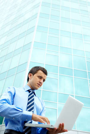 Young businessman working with laptop by office building photo