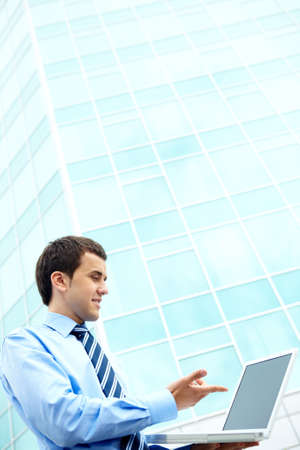 Young businessman using computer by office building photo