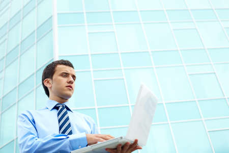 Businessman standing by office building and working with computer photo
