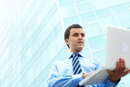 Businessman corresponding through internet by office building photo